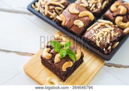 Chocolate Brownies With Cashew Nut And Peppermint On Wooden Plate On White Wooden Floor With Brownie