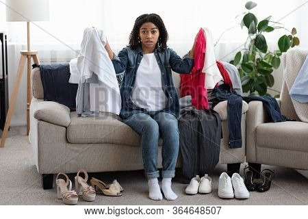 Clothing Dilemma Concept. Confused Black Woman Sitting On Messy Couch With Piles Of Clothes And Shoe