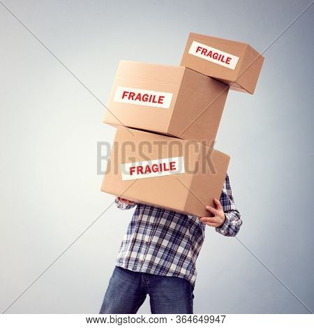 Man holding heavy fragile cardboard boxes relocation, moving house or courier delivery background
