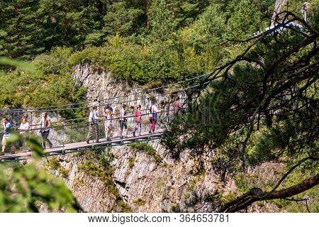 Altai Republic, Russia - 2019, People Walk On A Suspension Bridge Over A Precipice, Selective Focus
