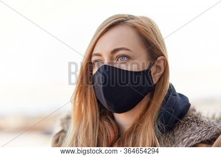health, safety and pandemic concept - young woman wearing black face protective reusable barrier mask outdoors