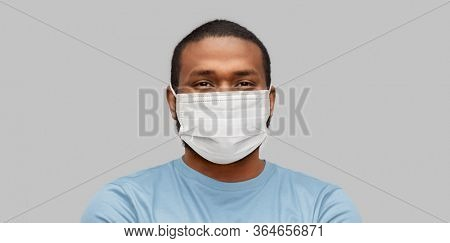 health, pandemic and safety concept - young african american man wearing face medical mask for protection from virus disease over grey background