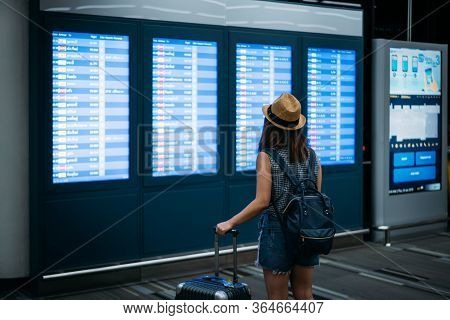 Young Woman Traveler Wearing Hat Holding Luggage Looking Boarding Times For Checking Flight In Inter