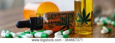 Close-up Of Medical Marijuana Products With Capsules And Cannabinoid Oil In Bottle With Marihuana Le