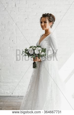 Bride With A Wedding Bouquet On A White Studio Brick Wall Background,wedding Dresses Catalog,beautif