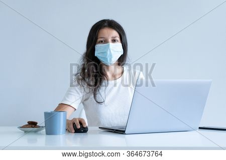 The Girl Works From Home During Quarantine. Corona Virus Pandemic. A Girl In A Surgical Mask Works O
