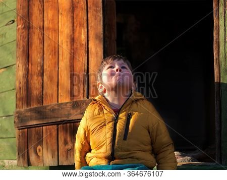 Outdoor Portrait Of A Dreamily Looking Kid Gazing At The Sky