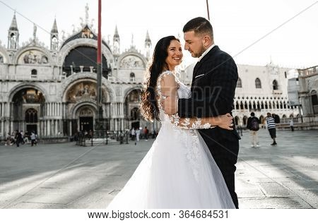 Happy Bride And Groom Cuddling While Walking Around The Old City Of Venice,groom Of Georgian Appeara