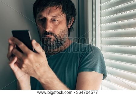 Man Text Messaging On Mobile Phone In Privacy Of His Bedroom Next To The Window With Closed Shutters