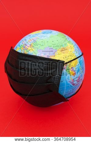 Terrestrial Globe Model With Black Surgical Mask Isolated On Red Background. Concept: Quarantined Ea