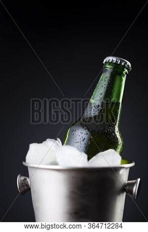 Close Up Of Beer Bottle In An Ice Bucket Filled With Ice Cubes Placed On A Bar Counter With Copy Spa