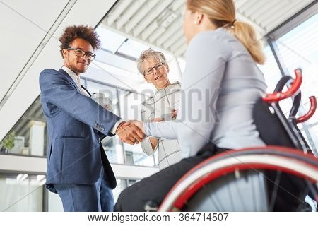 Young businessman greets colleague in wheelchair with handshake in the company