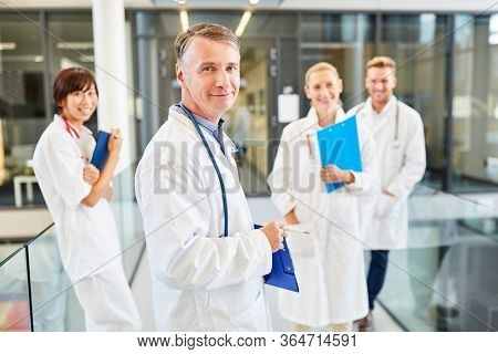 Successful senior physician and his competent medical team in the hospital
