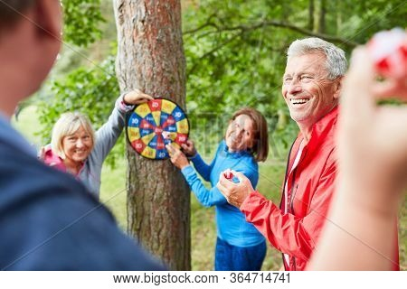 Group of seniors having fun while playing darts together in free time in nature