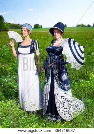Two Beautiful Young Women Dressed In Victorian Regency Jane Austen Style Fashion Dresses Strolling T