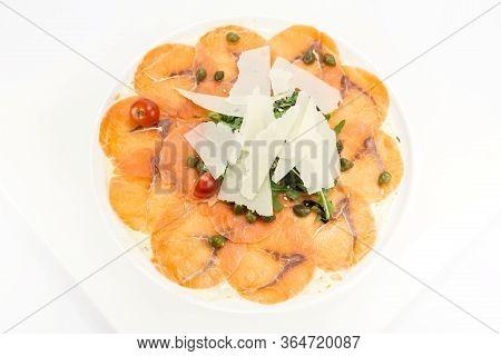 Salmon Sliced Carpaccio With Arugula And Sauce Closeup Shot In A Restaurant.