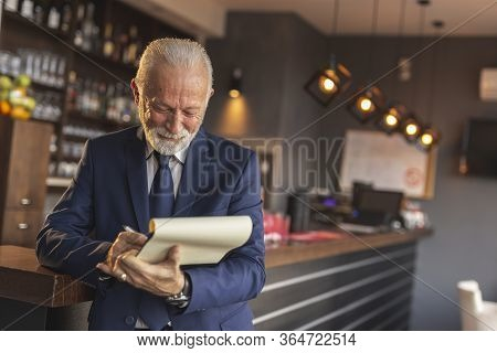 Restaurant Manager Standing Next To A Counter, Holding Documents, Signing Procurement And Supply Con