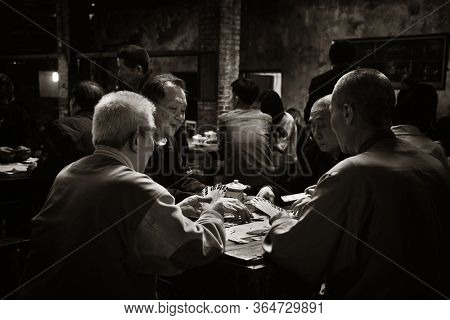 CHONGQING, CHINA – MARCH 13: Old men play cards on March 13, 2018 in Chongqing. The lifestyle of the old 80's is preserved in this Tea House as the famous tourism attracitions.