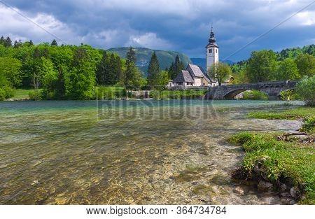 The Charming Little Church Of St. John The Baptist On Lake Bohinj, Julian Alps, The Largest Permanen