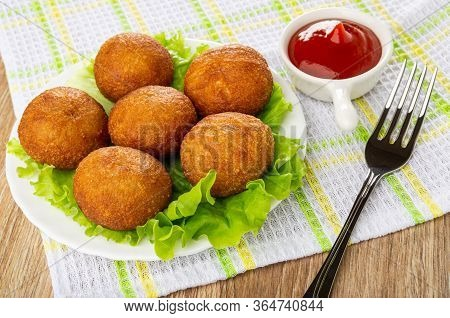 Small Round Fried Pies On Leaves Lettuce In White Glass Plate, Sauceboat With Ketchup, Fork On Check