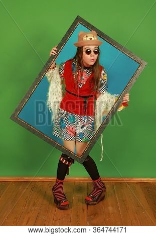 Funny Little Girl Freak Holds A Picture Frame In A Studio On A Green Background