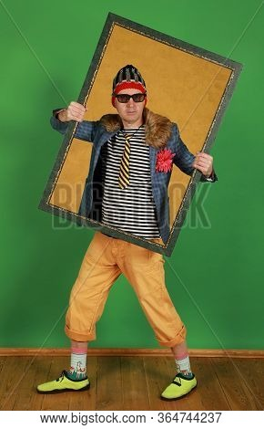 Middle Aged Male Freak Holds A Picture Frame In A Studio On A Green Background