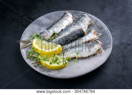 Fried sardines with lemon slices and herbs offered as closeup on a modern design plate with copy space