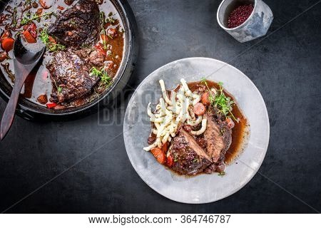 Traditional German braised beef cheeks in brown red wine sauce with noodles and carrots offered as top view on a modern design plate and stewpot on an old rustic board