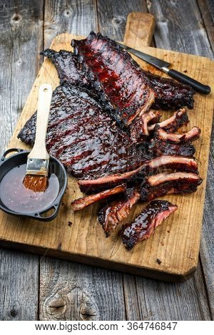 Barbecue veal spare loin ribs St Louis cut with hot honey chili marinade burnt as closeup on an old rustic wooden cutting board