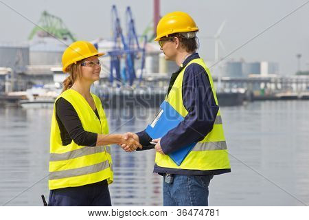 Two dockers greeting eachother in an industrial harbor, wearing the necessary safety gear