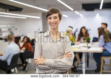 Successful young woman standing in front of businesspeople and smiling. Portrait of confident and proud businesswoman with team working in background at modern office. Business woman looking at camera