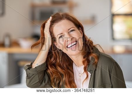 Portrait of cheerful beautiful woman touching hair after anti hair loss treatment. Successful mature woman at home smiling looking at camera. Middle aged redhead woman in casual laughing.