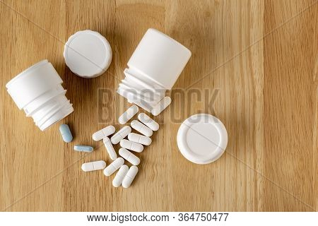 Two White Bottles Of Tablets And A Series Of White And Blue Pills