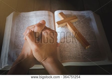 The Crucifix Lay On The Bible. And The Hand Of A Young Woman Seeking Divine Blessing With The Power
