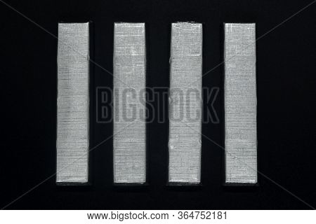 Paralleled Chocolate Bars In Silver Packaging On Background
