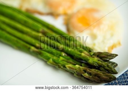 Close Uo Of Baked Roasted Fresh Green Asparagus With Fried Eggs Under Parmesan Cheese In Big White P
