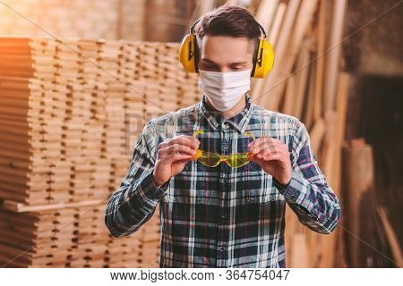 Portrait Male Carpenter In Protective Headphones On Ears, Medical Mask On Face Wearing Protective Gl