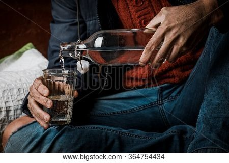 Alcohol Problem. A Man Holds A Bottle Of Alcohol In His Hand. Problem With Alcohol Addiction, Alcoho