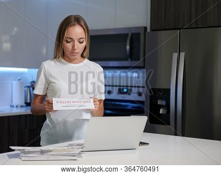 Worried Young Female With Laptop Reading Eviction Letter In The Kitchen