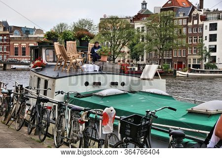 Amsterdam, Netherlands - July 8, 2017: Person On A Houseboat Deck On Amstel River In Amsterdam, Neth