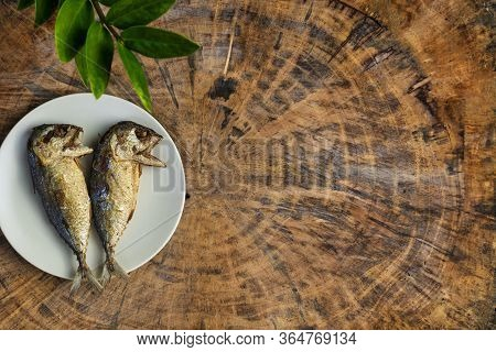 Top View Fried Mackerel On A White Plate With Real Wooden Table With Copy Space For Text Or Design.