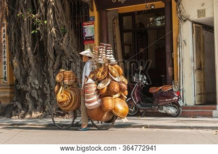 Hoi An Vietnam October 20 2013; Traveling Hat And Basket Salesman With His Entire Stock Arrayed On H