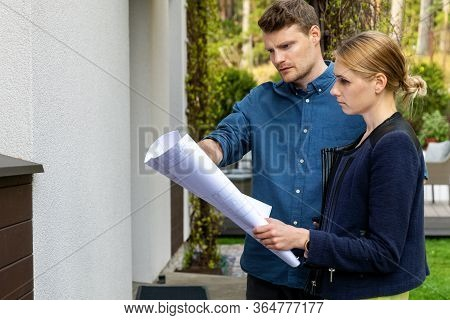 Young Couple Looking At Blueprints Of House They Want To Buy