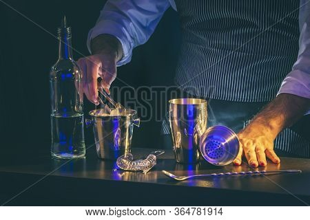 Bartender Making A Cocktail, Adding Ice Cubes From An Ice Bucket Into A Cocktail Shaker