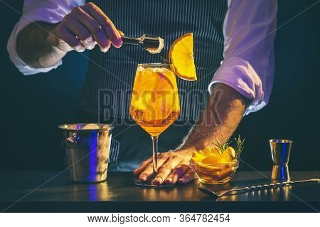 Bartender Adding Ice Cubes From Ice Bucket Into Aperol Spritz Cocktail Glass; Barman Serving Orange