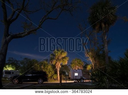Teardrop camper in campsite at Hunting Island State park, South Carolina at night with stars.