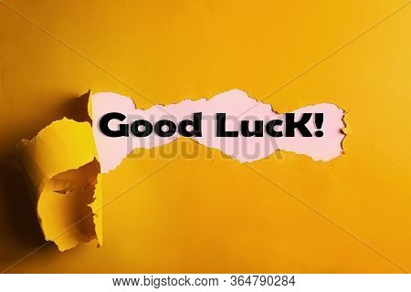 Phrase Good Luck On Pink Background, View Through Hole On Yellow Paper