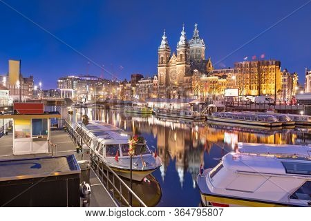 Amsterdam, Netherlands city center view with riverboats and the  Basilica of Saint Nicholas at night.