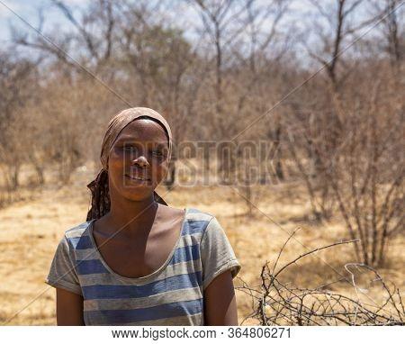 Motswana, African woman in the bush next to a tree , Kalahari in Botswana