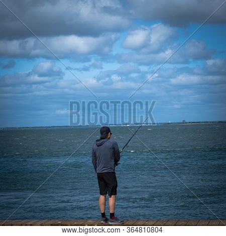 Barnegat, Nj, Usa -- September 13, 2019. Photo Of A Young Man Fishing In Barnegat Bay From The Board